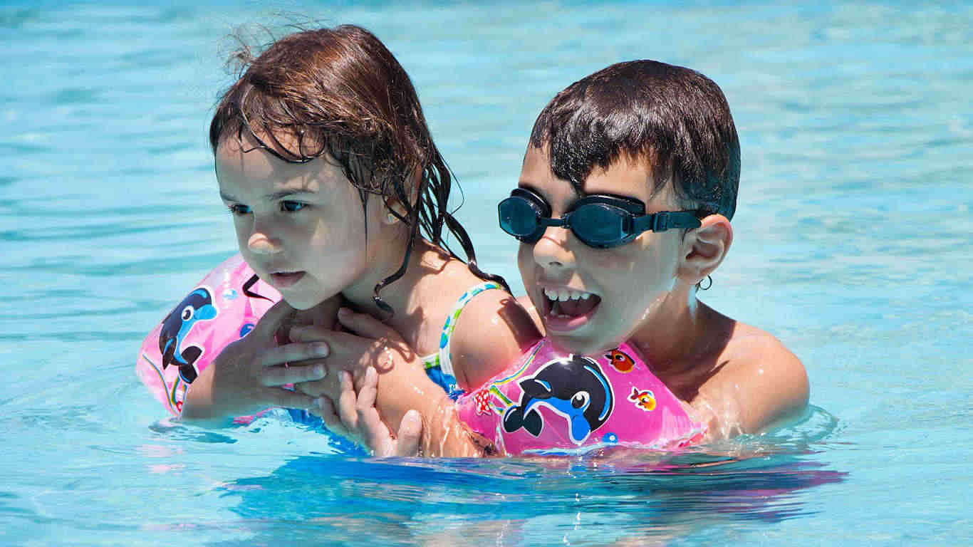 Happy little brother embracing his sister in a swimming pool